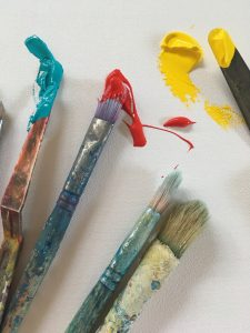 Photograph of paint brushes with turquois, red and yellow paint