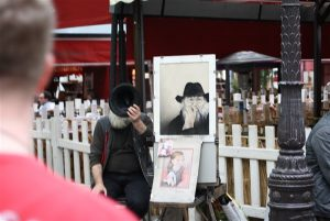 Montemartre artist covering his face whilst sitting next to a self portrait